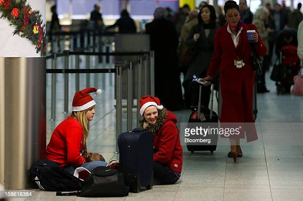 Passengers wear festive Santa Claus hats as they sit with their luggage in the checkin area of the south terminal at Gatwick airport in Crawley UK on...
