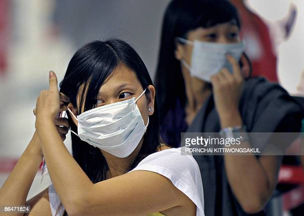 Passengers wear masks as they arrive at the Suvarnabhumi airport in Bangkok on May 7 2009 The World Health Organisation urged Asian nations to remain...