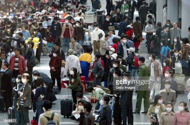 Passengers wear masks to protect against the SARS virus as they wait April 24 2003 at the Beijing Airport in Beijing China Thousands have been...