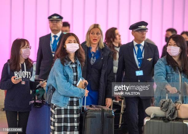 Passengers wear masks to protect against the spread of the Coronavirus as they arrive at the Los Angeles International Airport California on January...