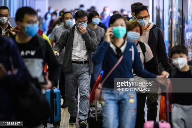 TOPSHOT Passengers wear protective face masks as they arrive from Shenzhen to Hong Kong at Lo Wu MTR station hours before the closing of the Lo Wu...