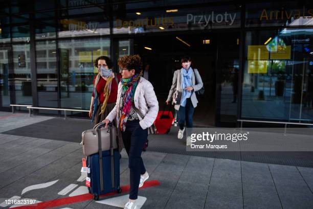 Passengers wear protective face masks as they arrive from Warsaw at the terminal of John Paul II Krakow International Airport on June 1, 2020 in...