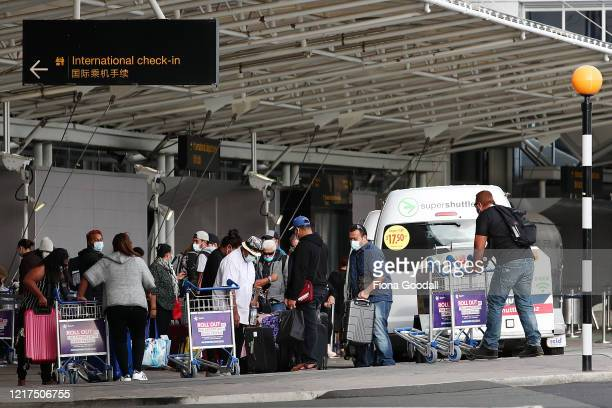 Passengers wear protective masks and gloves at Auckland International Airport on April 08, 2020 in Auckland, New Zealand. New Zealand has been in...