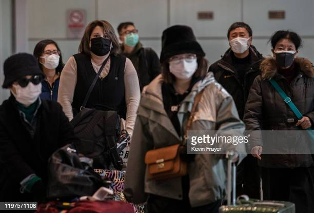 Passengers wear protective masks as they arrive at Beijing Capital Airport on January 30 2020 in Beijing China The number of cases of a deadly new...