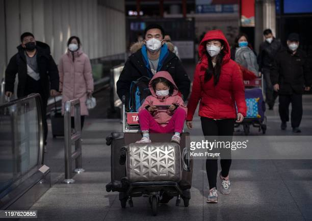 Passengers wear protective masks as they walk he their luggagein the arrivals area at Beijing Capital Airport on January 30 2020 in Beijing China The...