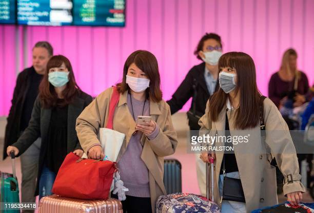 TOPSHOT Passengers wear protective masks to protect against the spread of the Coronavirus as they arrive at the Los Angeles International Airport...
