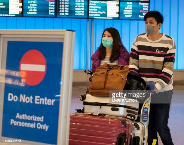 Passengers wear protective masks to protect against the spread of the Coronavirus as they arrive at the Los Angeles International Airport California...