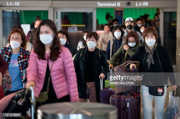 Passengers wear protective masks to protect against the spread of the Coronavirus as they arrive on a flight from Asia at the Los Angeles...