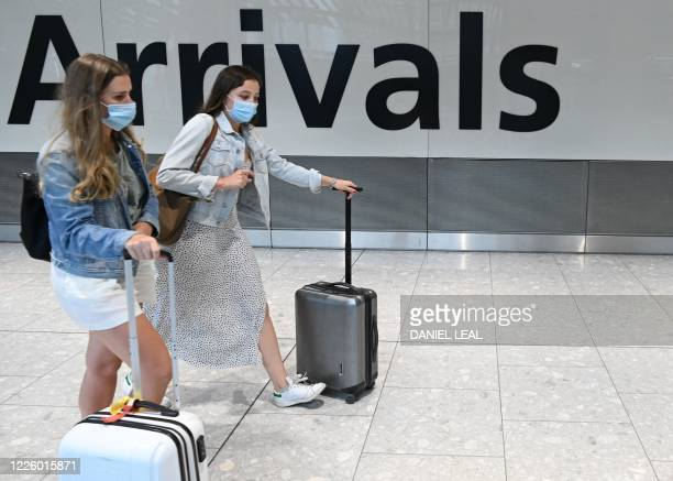 Passengers wearing a face mask or covering due to the COVID-19 pandemic, arrive at Heathrow airport, west London, on July 10, 2020. - The British...