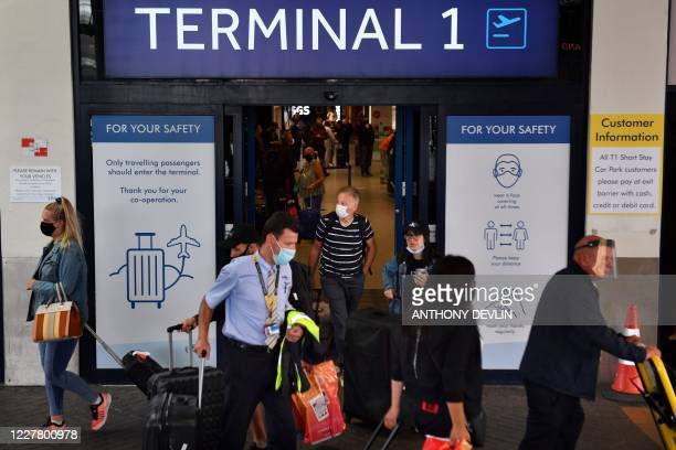 Passengers wearing a face mask or covering due to the COVID19 pandemic react as they exit Terminal 1 after landing at Manchester Airport in...