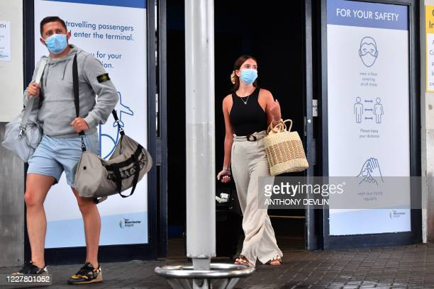 Passengers wearing a face mask or covering due to the COVID-19 pandemic, react as they exit Terminal 1 after landing at Manchester Airport in...