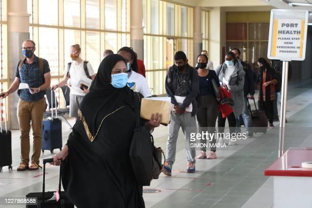 Passengers wearing a protective mask walk-in at the Jomo Kenyatta international airport in Nairobi, on August 1 as Kenya Airways airline resumed...