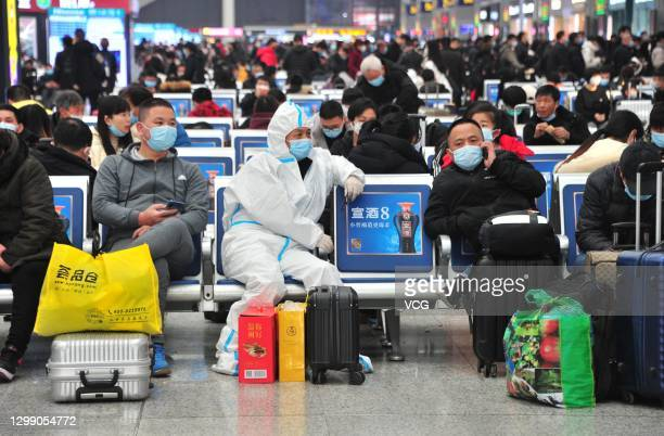 Passengers wearing face masks and personal protective equipment wait for their trains at Hongqiao Railway Station one day before the Spring Festival...