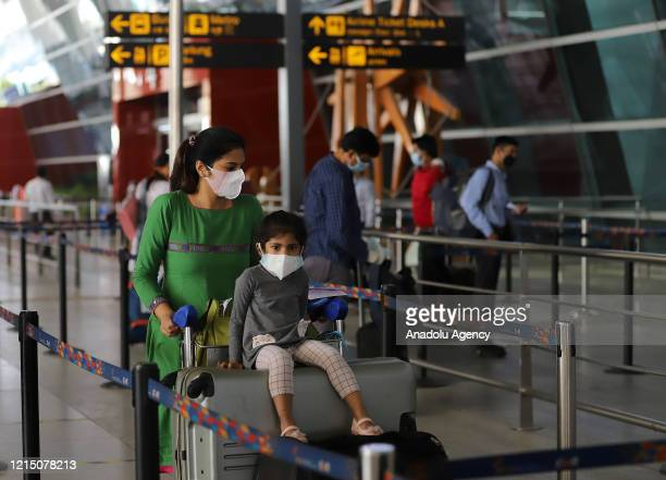 Passengers wearing face masks arrive at Indira Gandhi International airport after the government allowed domestic flight services to resume during an...