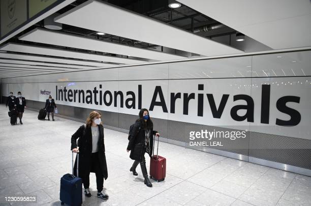 Passengers wearing face masks as a precautionary measure against COVID-19, walk through the arrivals hall after landing at London Heathrow Airport in...