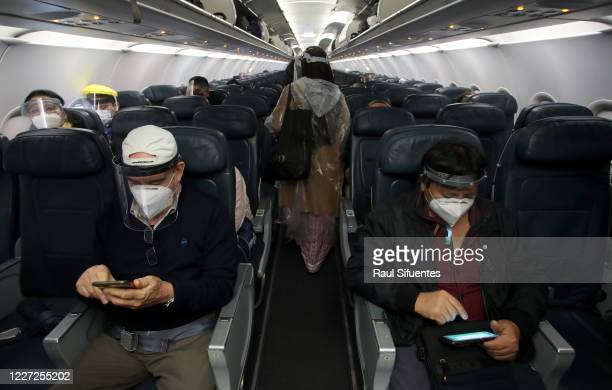 Passengers wearing face masks check their mobile phones as they sit on the plane before the LA 2212 flight from Lima to Trujillo, Peru takes off on...