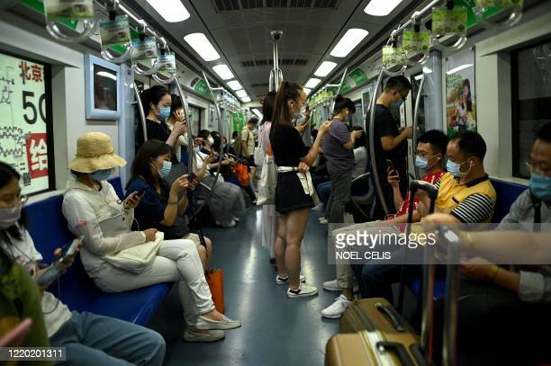 Passengers wearing face masks commute on a subway train during rush hour in Beijing on June 15, 2020.