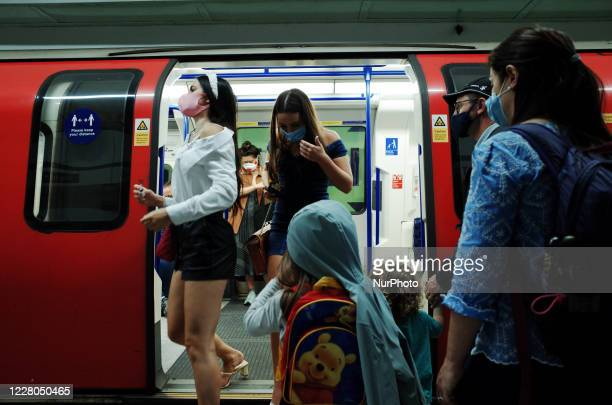 Passengers wearing face masks, currently mandated on public transport, disembark from a Northern line tube service at Tottenham Court Road station in...