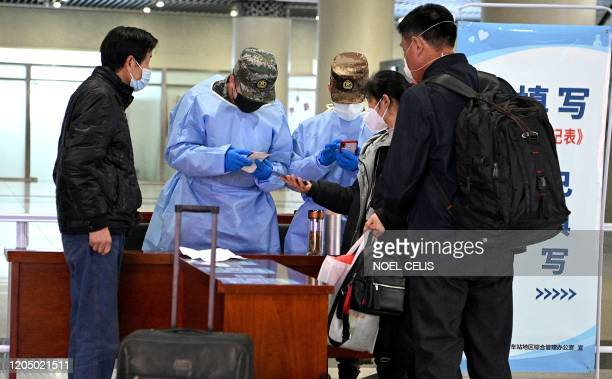 Passengers wearing face masks have their travel history checked as they arrive at the railway station in Hefei, Chinas eastern Anhui province on...