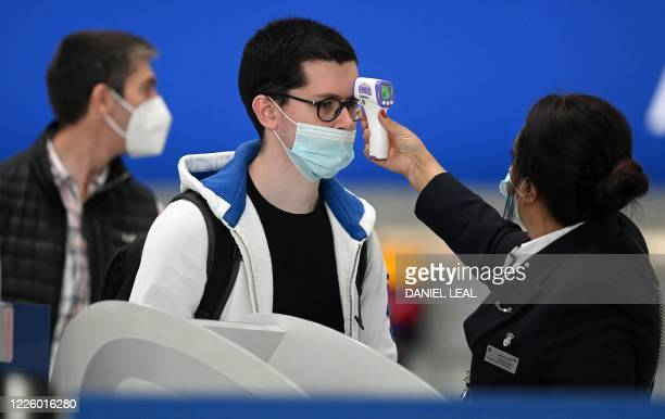 Passengers wearing face masks or covering due to the COVID-19 pandemic, have their temperature taken as they queue at a British Airways check-in desk...
