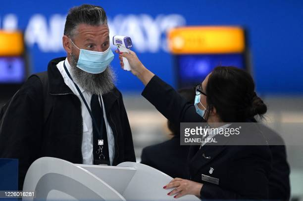 Passengers wearing face masks or covering due to the COVID19 pandemic have their temperature taken as they queue at a British Airways checkin desk at...