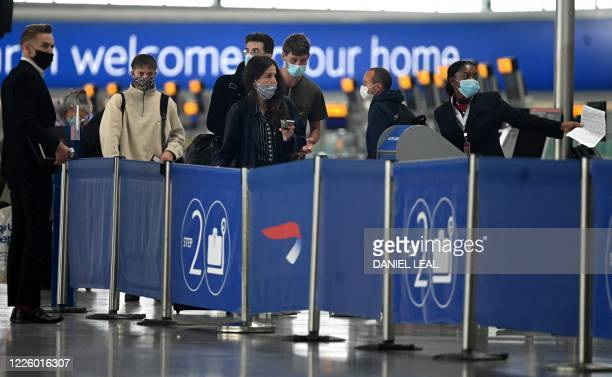 Passengers wearing face masks or covering due to the COVID-19 pandemic, queue at a British Airways check-in desk at Heathrow airport, west London, on...