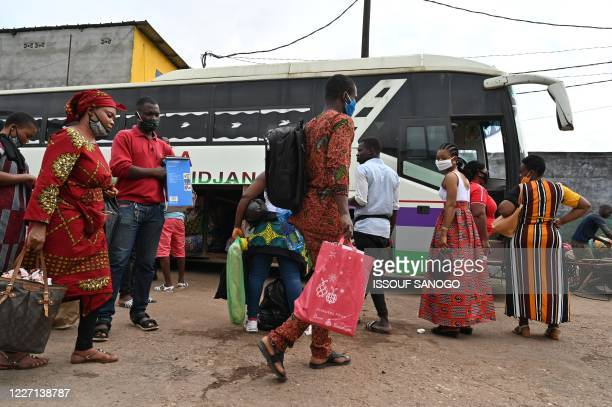 Passengers wearing face masks prepare to board a bus at the Adjame bus station in Abidjan on July 15 on the first day of the lifting of travel...