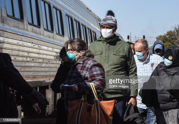 Passengers wearing face masks prepare to board a train at the Orlando Amtrak station on the first day that the Transportation Security Administration...