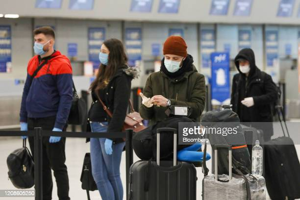 Passengers wearing face masks prepare to checkin at London Luton Airport in Luton UK on Monday March 30 2020 EasyJet Plc grounded its entire fleet...