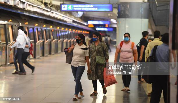Passengers wearing face masks to prevent the spread of coronavirus arrive to board a metro train at Mandi House after metro services resumed during...