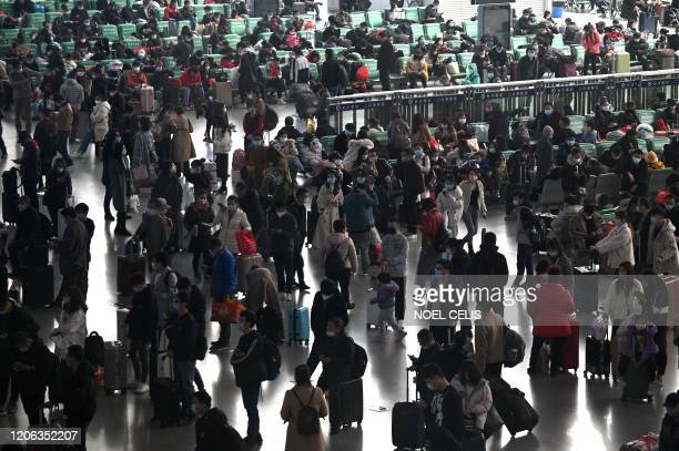 Passengers wearing face masks wait for their trains at Changsha railway station in Changsha, China's central Hunan province on March 10, 2020. -...