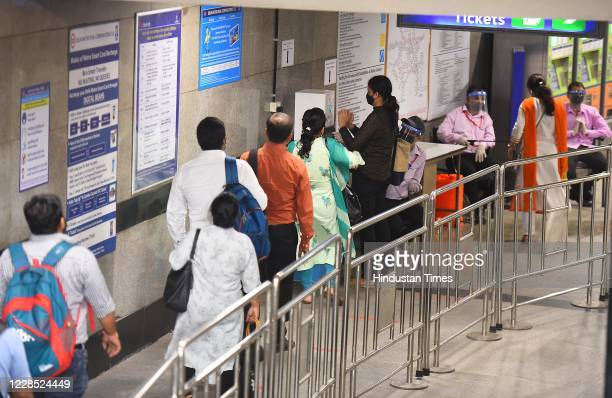 Passengers wearing face masks wait to sanitize their hands before entering Mandi House metro station after the metro resumed its services during...