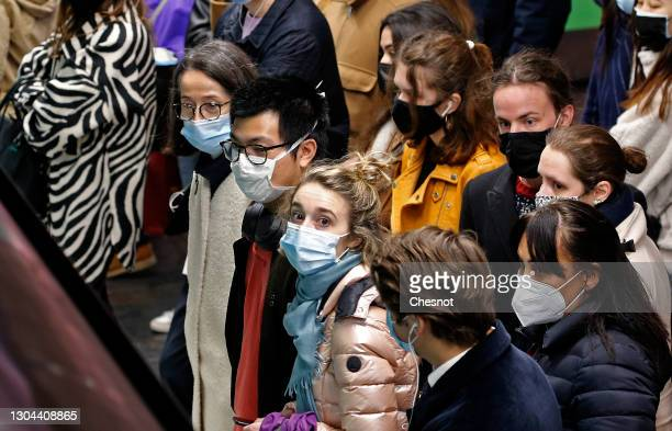 Passengers wearing face protective masks wait on the platform shortly before the curfew which begins at 6 p.m., during the coronavirus disease...
