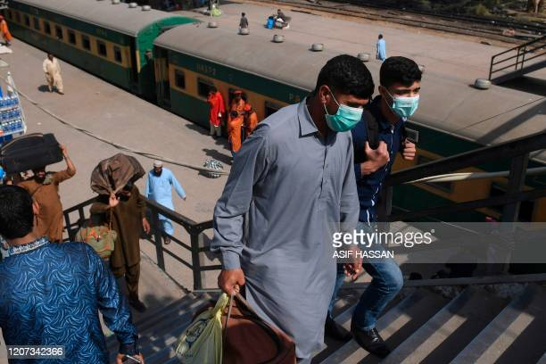 Passengers wearing facemasks amid concerns over the spread of the COVID-19 novel coronavirus, arrive at Karachi Cantonment railway station in Karachi...