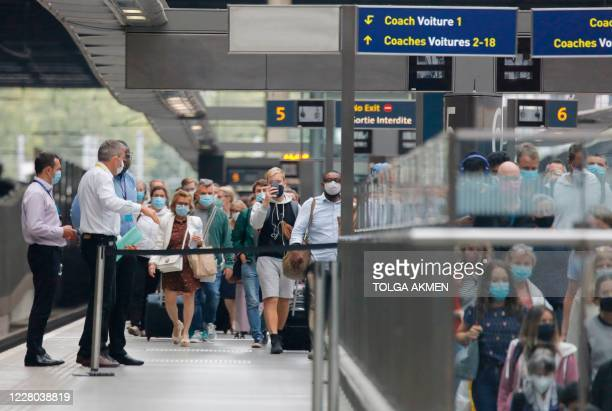 Passengers wearing facemasks as a precaution against the spread of the novel coronavirus walk along the platform to an escalator after arriving on a...