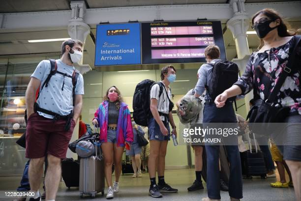 Passengers wearing facemasks as a precaution against the spread of the novel coronavirus walk through arrivals onto the main concourse at St Pancras...