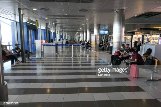 Passengers wearing facemasks, face shields, gloves and other safety measures are seen in the airport terminal before departing for a flight, at...