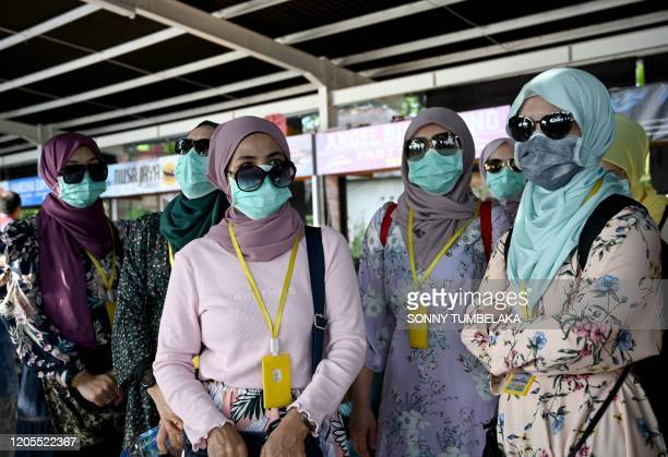 Passengers wearing facemasks prepare to board fast boats to cross from Sanur to Nusa Penida island, on Indonesia resort island of Bali on March 7,...