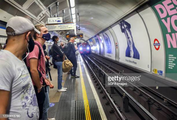 Passengers wearing facemasks wait to get on a northbound Bakerloo train. Despite the end of the legal requirement to wear facemasks in England,...