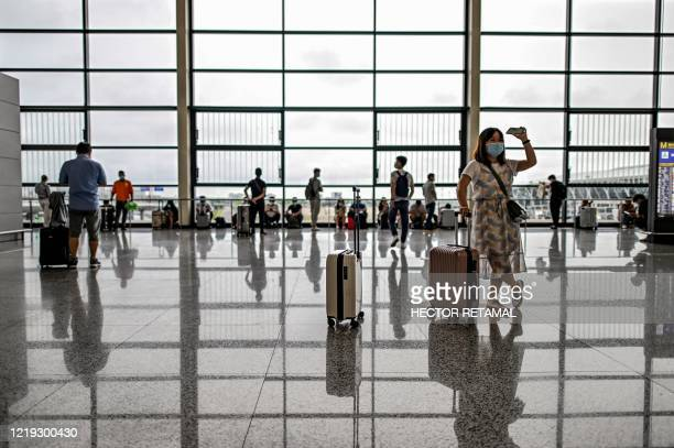 Passengers wearing facemasks walk across a hall following preventive procedures against the spread of the COVID-19 coronavirus in Pudong...