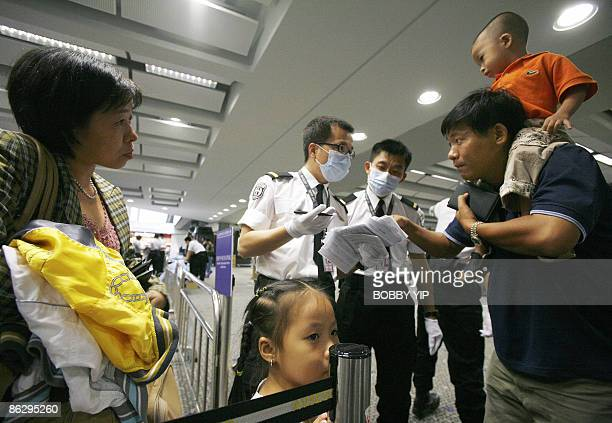 Passengers wearing masks are asked to fill in health declaration forms upon their arrival at the Hong Kong Airport in Hong Kong on April 30 2009 The...
