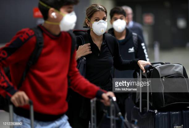 Passengers wearing masks arrive at Dulles International Airport March 13 2020 in Dulles Virginia US President Donald Trump announced restrictions on...