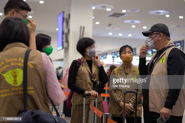 Passengers wearing masks queue at the immigration counter at the Kuala Lumpur International Airport 2 arrival hall on February 4, 2020 in Kuala...