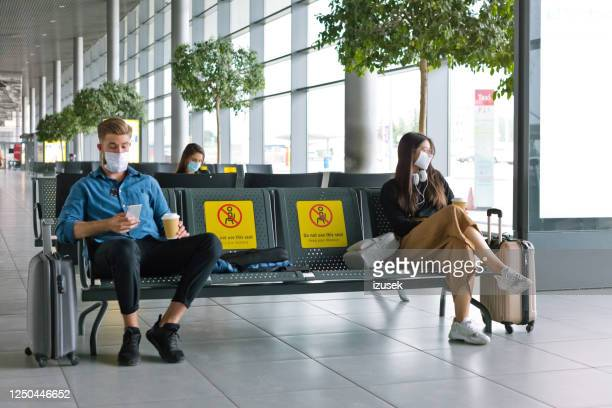 passengers wearing n95 face mask waiting in airport area - airport stock pictures, royalty-free photos & images