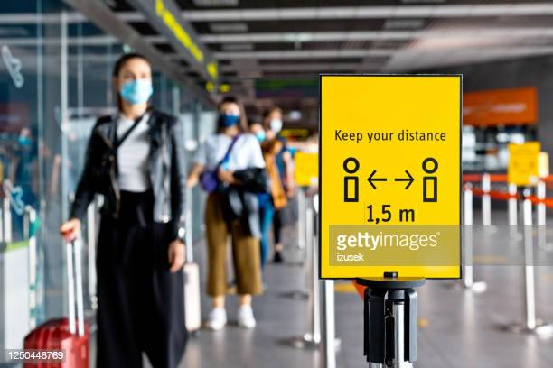 passengers wearing n95 face masks waiting in line at airport terminal - airport stock pictures, royalty-free photos & images