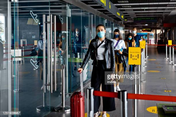 passengers wearing n95 face masks waiting in line at airport terminal - aeroplane stock pictures, royalty-free photos & images