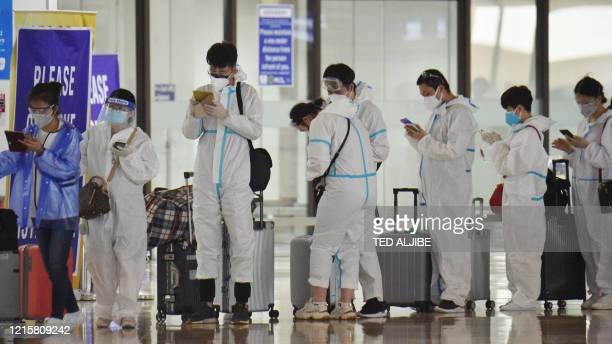 Passengers wearing personal protective suits queue up at the check-in area at the international airport in Manila on May 28 for their commercial...