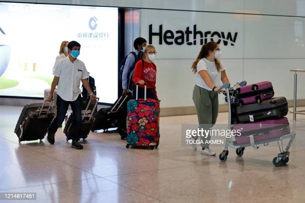 Passengers wearing PPE arrive at Terminal 2 of Heathrow airport, west London on May 22, 2020.