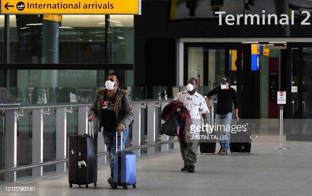 Passengers wearing PPE including a face mask as a precautionary measure against COVID19 walk through the arrivals hall after landing at at Terminal...