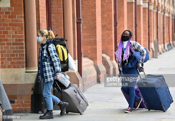Passengers wearing PPE , including a face mask as a precautionary measure against COVID-19, pull their suitcases as they arrive at St Pancras...